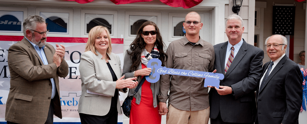 """A military family receives the """"key"""" to their new home courtesy of Freedom Alliance's Heroes to Homeowners project."""