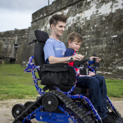 Man rides track chair with toddler